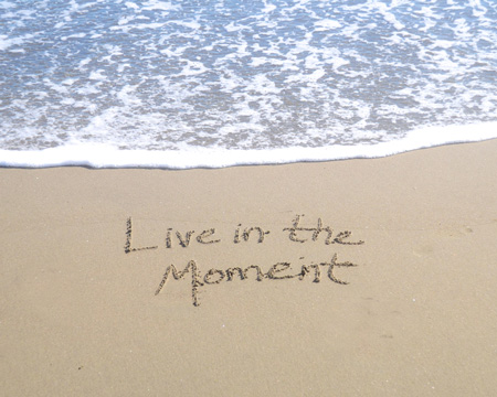 Live in the Moment written in sand on the beach