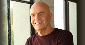 Dr. Wayne W. Dyer onstage, wearing a shirt that says Love